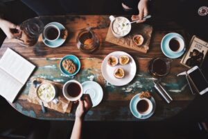 person-sitting-near-table-with-teacups-and-plates-2074130